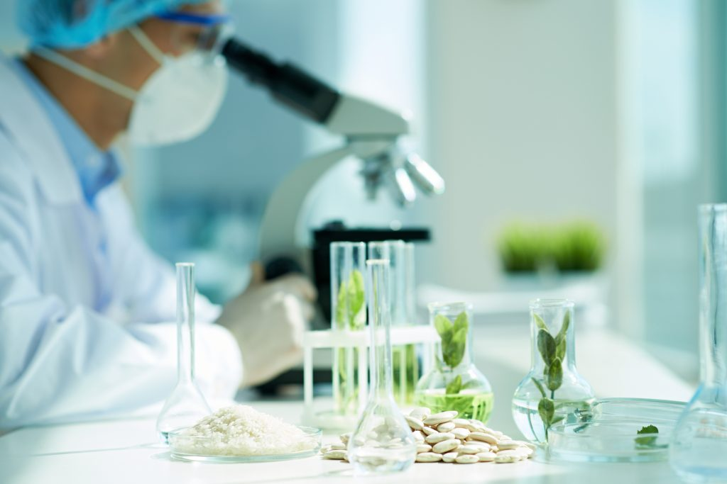White beans and green leafs in flasks on the table with biologist in the background - illustration société Laboratoire Lescuyer